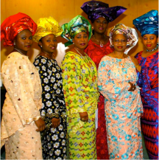 Nigerian women in modern outfits, consisting of boubous and head ties.