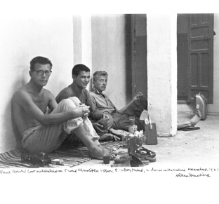 Paul Bowles, in Marrakesh, furthest from the camera, with his leg outstretched (1962).