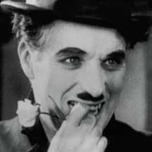 """Charlie Chaplin as the Tramp in """"City Lights"""" - after having just been recognized by the girl he once saved. His face shows both agony and joy."""