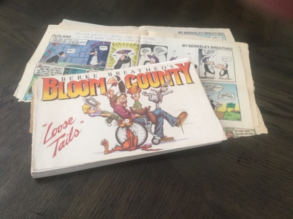 """Bloom County - Loose Tails"", by Berke Breathed. The cover of my very well-read and loved-to-pieces copy of the first Bloom County collection. Laid on some newspaper clippings of Breathed's ""Outland"" strip, which also featured ""Opus"". These were sent to me all the way to South Africa from the USA. Launch date: Dec. 8, 1980; end date Aug. 6, 1989, resumed on July 13, 2015."