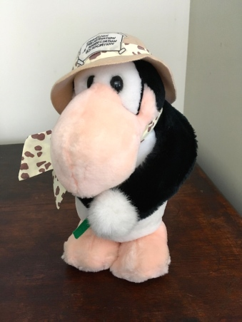 "My ""Opus"" plush toy, carefully kept all these years. He is holding a dandelion and his hat has a label on it that says ""Dandelion Preservation Society""."