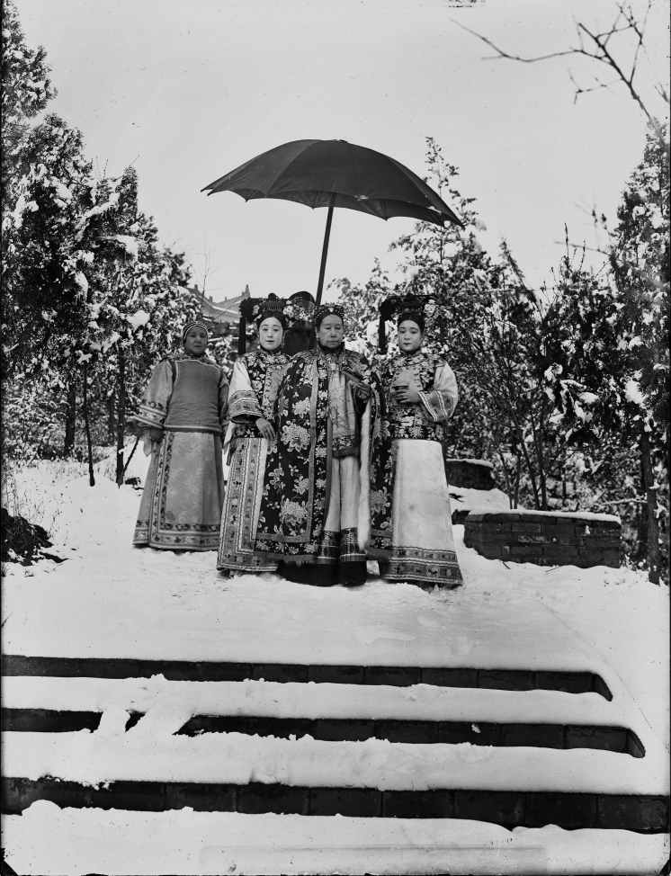 Cixi, accompanied by her attendants, stands in the snowy gardens of Wanshoushan (Longevity Hill), the central hill of the Summer Palace. The image is one of nine similar photographs that were most likely taken for the enjoyment of the empress and her attendants — not for any diplomatic purpose. (Source: Freer Gallery of Art and Arthur M. Sackler Gallery, SC-GR 259) Retrieved from: https://www.npr.org/2011/12/19/143796431/powerful-portraits-capture-chinas-empress-dowager