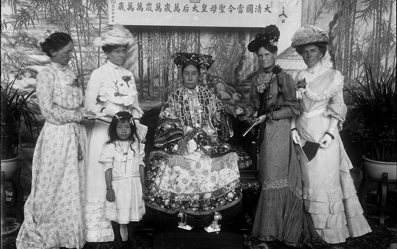 """This photograph shows Empress Cixi seated on her throne in front of a banner that declares her full title, showing her ornate """"horse-hoof"""" platform shoes. (Source: Freer Gallery of Art and Arthur M. Sackler Gallery SC-GR-254) Retrieved from: https://www.npr.org/2011/12/19/143796431/powerful-portraits-capture-chinas-empress-dowager"""
