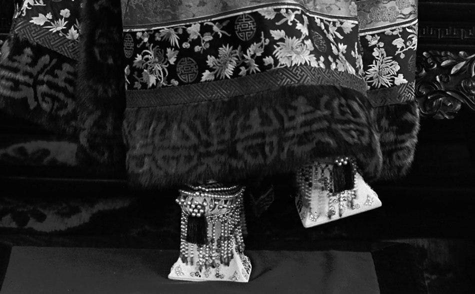 """This photograph is a closeup of Empress Cixi seated on her throne in front of a banner that declares her full title, showing her ornate """"horse-hoof"""" platform shoes. (Source: Freer Gallery of Art and Arthur M. Sackler Gallery SC-GR-254) Retrieved from: https://www.npr.org/2011/12/19/143796431/powerful-portraits-capture-chinas-empress-dowager"""